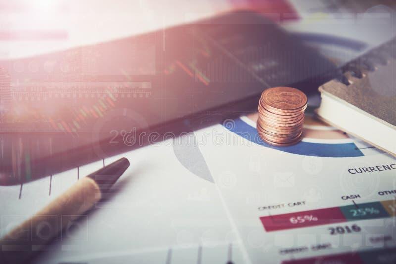 硬币和电话打开屏幕、技术图表、投资综合报告和企业设备在书桌上 投资 库存照片
