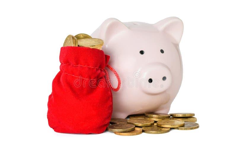 硬币和红色布料袋子的存钱罐充满在白色背景隔绝的硬币 免版税库存图片