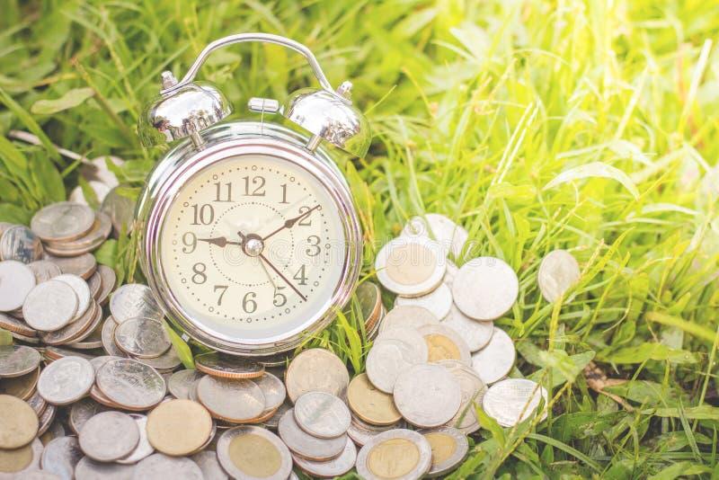 硬币和闹钟在绿草,金钱被安置,财政 免版税库存图片