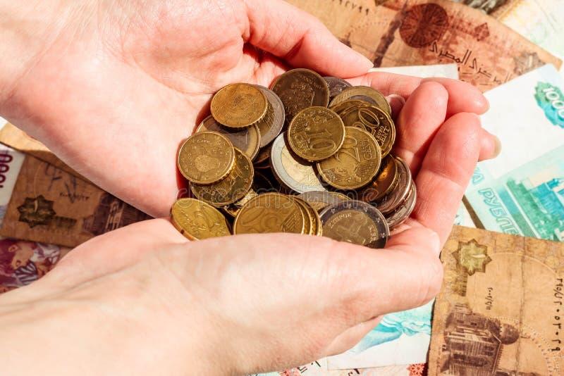 硬币在女性手上 五颜六色的钞票背景 安全金钱概念 免版税库存图片