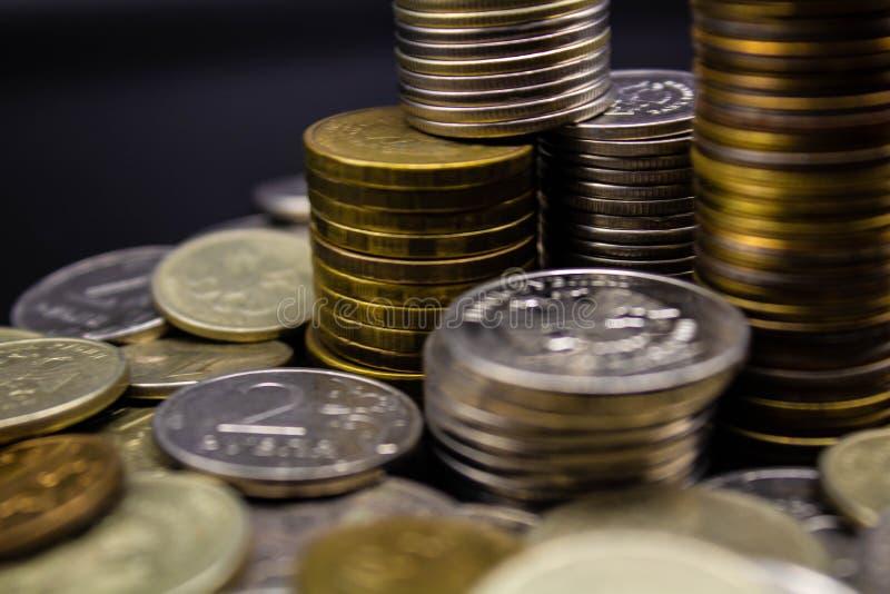 硬币在概念墙壁的黑背景和在黑背景的强的moneycoins堆积 免版税图库摄影