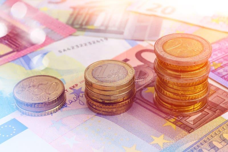 硬币在欧洲钞票绘制 图库摄影