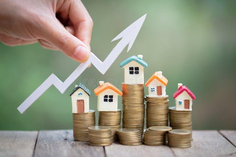 硬币堆、增长的事务、物产投资和房子抵押财政概念的微型式样房子 库存照片