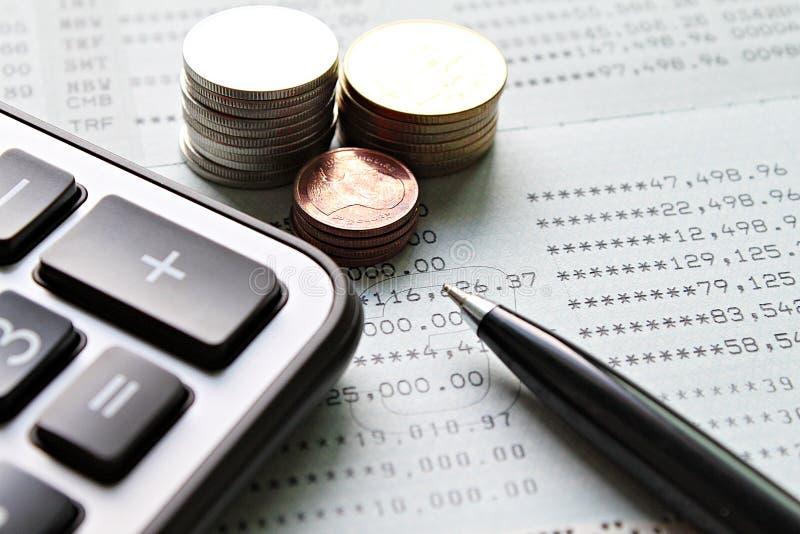 硬币堆、计算器、笔和储蓄账户存款簿或者财政决算在办公桌桌上 图库摄影