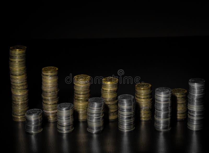 硬币堆两行  银和在黑暗的背景隔绝的金币堆 库存图片