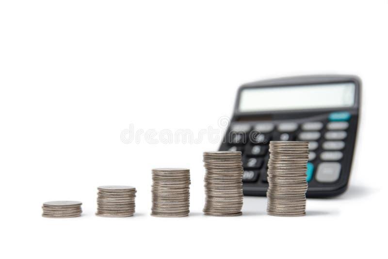 硬币堆和计算器在白色背景 库存图片