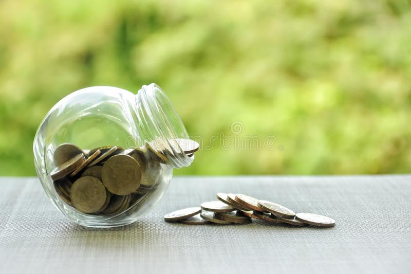 硬币溢出在水罐外面有绿色背景 免版税库存图片