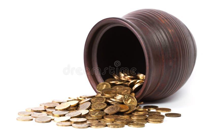 硬币落的金黄罐 免版税库存照片