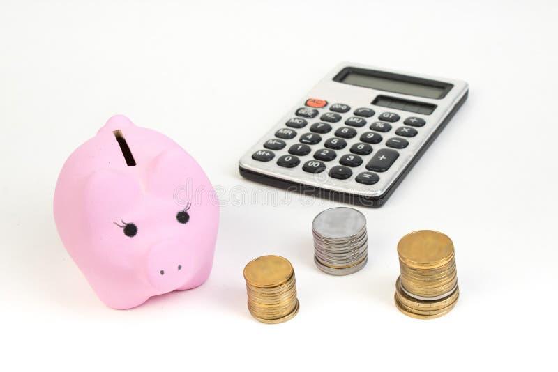 硬币,计算器,白色被隔绝的背景的桃红色存钱罐 免版税库存图片