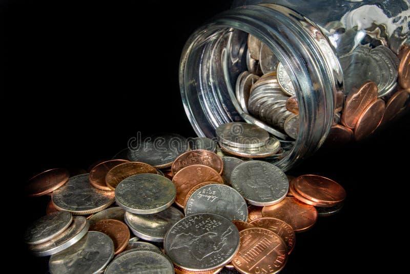 硬币从在黑背景的一个金属螺盖玻璃瓶溢出 免版税库存照片