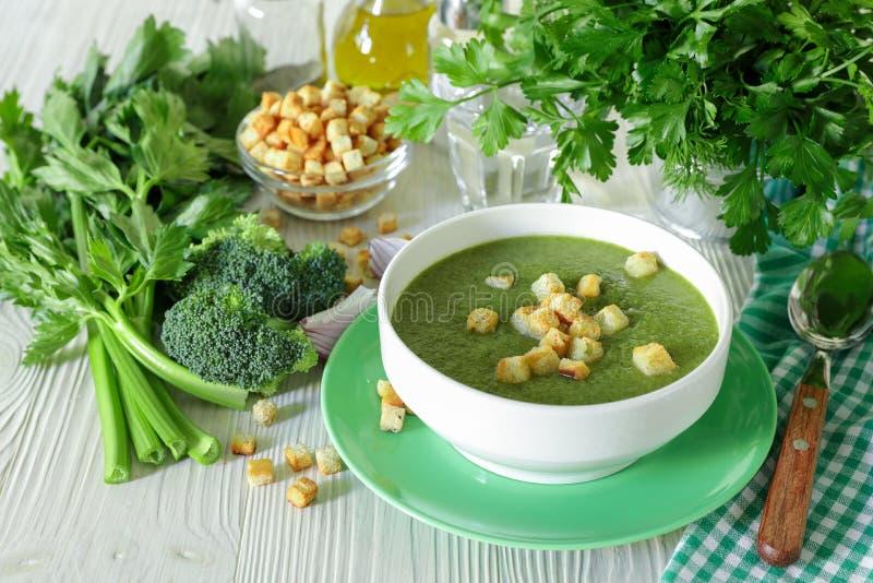 硬花甘蓝、芹菜和草本健康汤纯汁浓汤用油煎方型小面包片 免版税库存图片