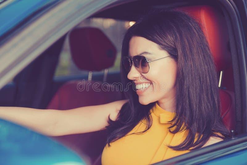 确信和美丽 黄色礼服的可爱的妇女在她新的现代汽车 库存图片