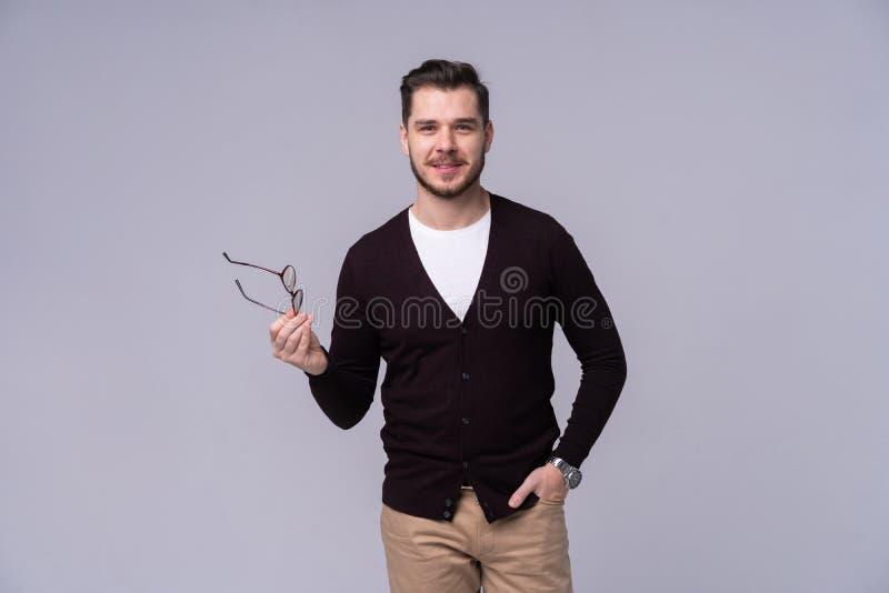 确信地摆在与在灰色背景的大微笑的镜片的年轻愉快的人 免版税库存照片