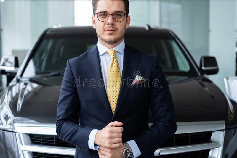 确信对他的选择 formalwear身分在汽车前面和看的照相机成熟灰色头发人 免版税库存图片