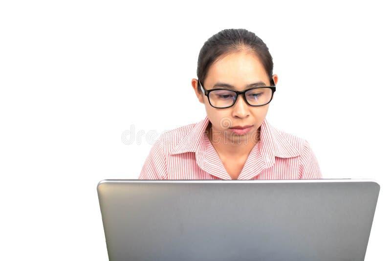 确信的亚裔妇女,戴着眼镜接近的画象与膝上型计算机一起使用,严重看与面孔的照相机,坐 免版税图库摄影
