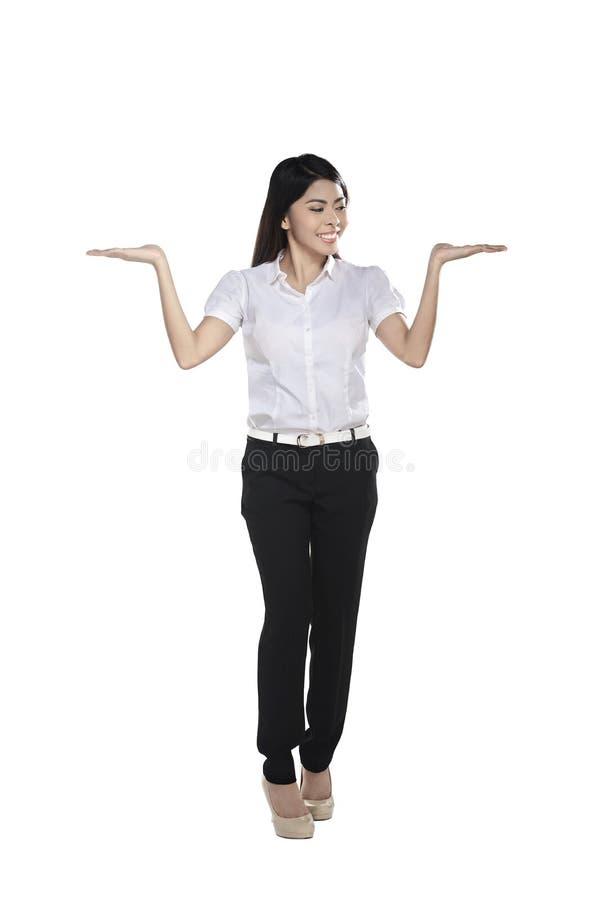 确信的亚洲女商人展示某事 免版税库存照片