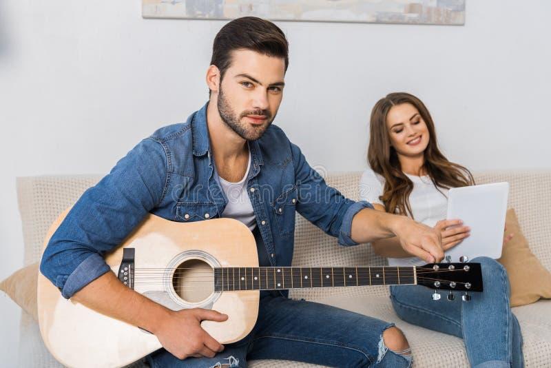 确信的人调整的吉他和看照相机,当他的女朋友时 图库摄影