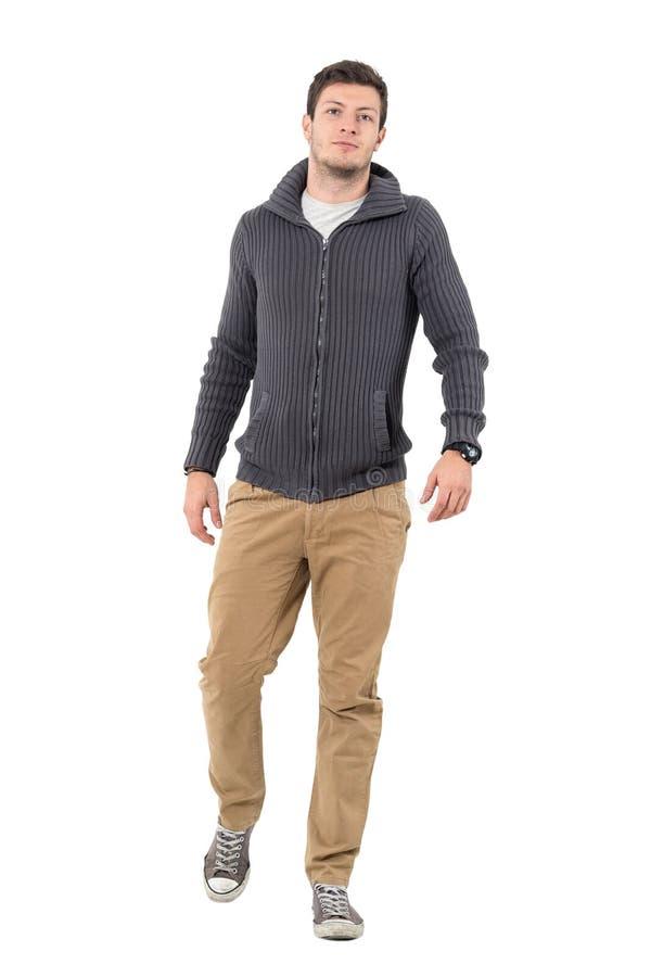 年轻确信的偶然走往照相机的人佩带的邮编毛线衣 免版税图库摄影