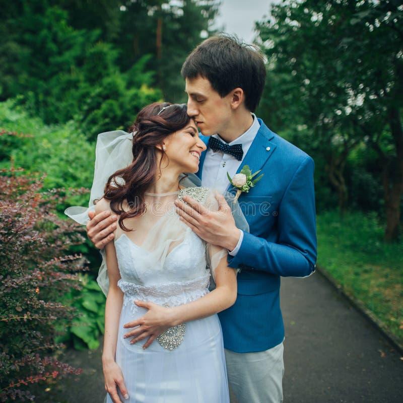 确信的典雅的拿着手ou的新郎和美丽的害羞的新娘 免版税库存照片