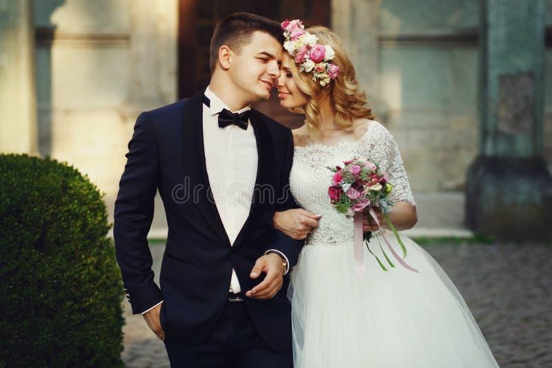 确信的典雅的拿着手ou的新郎和美丽的害羞的新娘 免版税库存图片