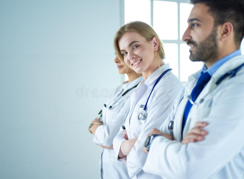 确信的医生画象有胳膊的横渡在医疗办公室 免版税库存照片