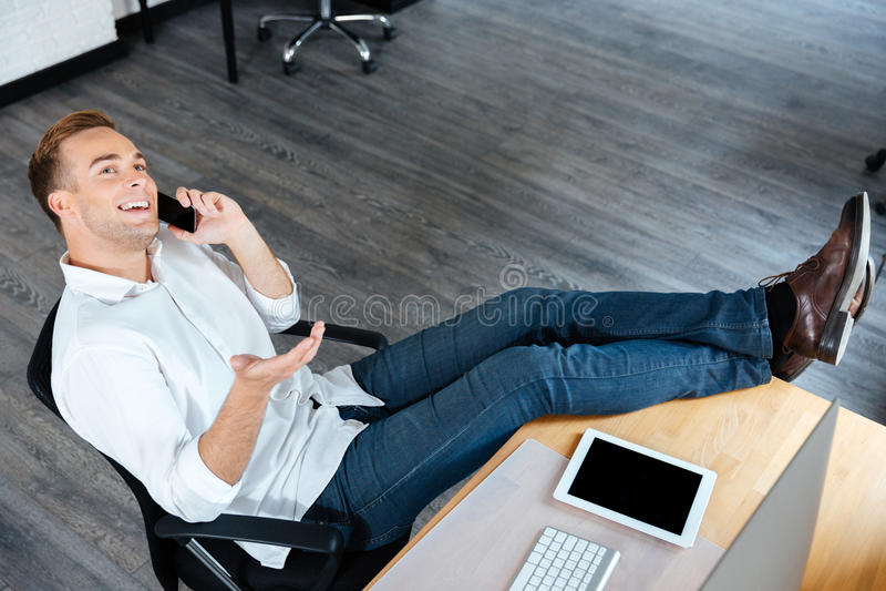 确信的商人和谈话坐手机在工作场所 免版税库存照片