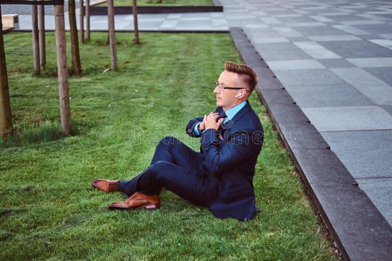 确信的商人在典雅的衣服穿戴了坐绿色草坪反对都市风景背景 免版税库存图片