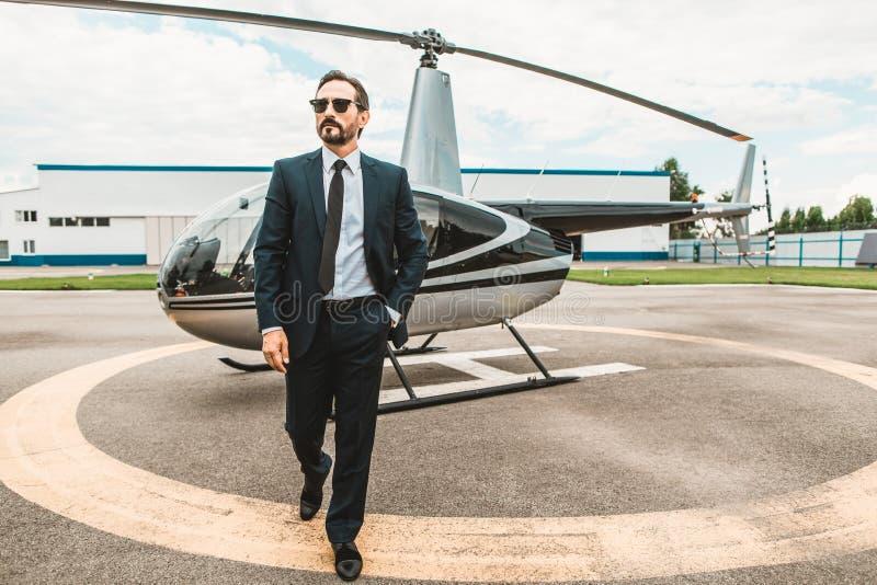 确信的商人戴着眼镜和走从直升机 库存照片