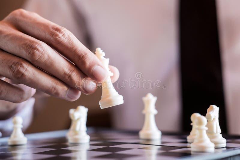 确信的商人用途国王棋子白色使用的下棋比赛的手对发展分析新的战略计划,事务的 免版税库存图片