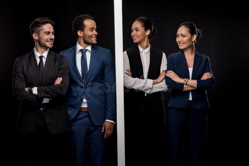 确信的商人由有微笑的女实业家的墙壁分离了 库存照片