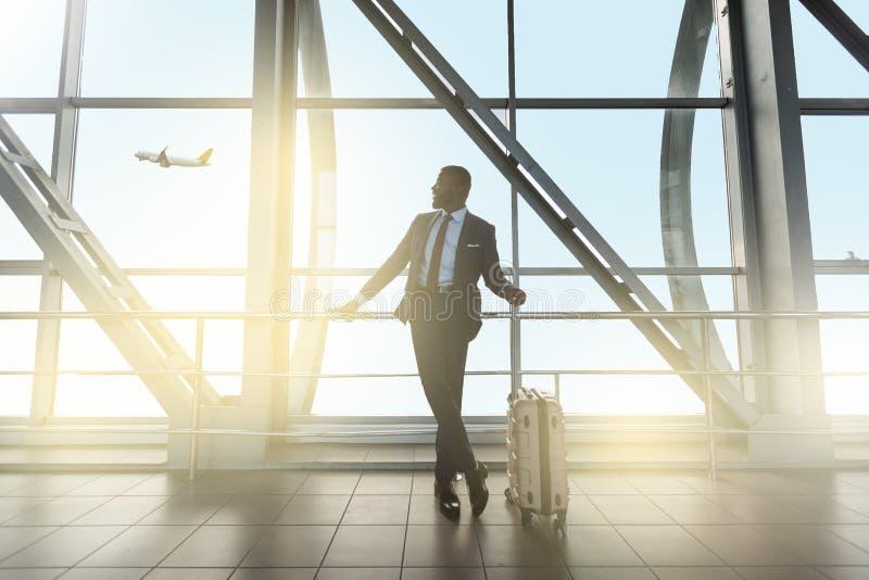 确信的商人等待的飞行在机场终端 ?? 免版税图库摄影