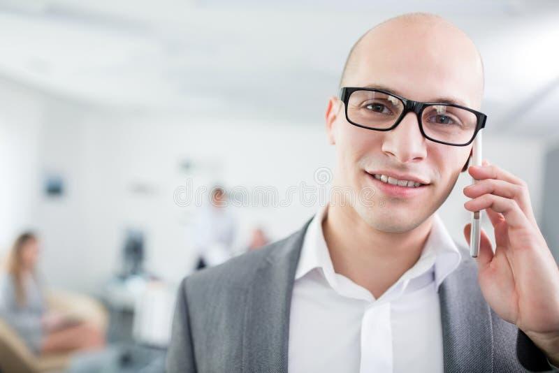 确信的商人谈话在智能手机在办公室 库存图片
