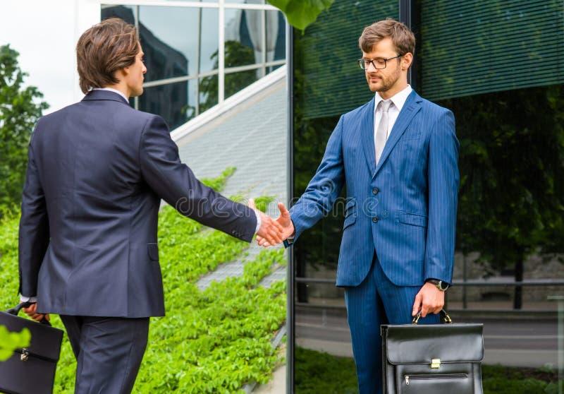 确信的商人谈话在现代办公楼前面 商人和他的同事 开户和财政 免版税库存照片