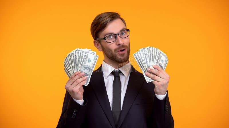 确信的商人陈列美元钞票,高收入的工作,现金报酬 库存图片