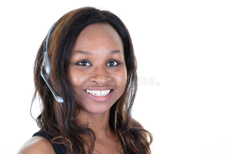 确信的在书桌的妇女客服代理佩带的耳机 免版税库存图片