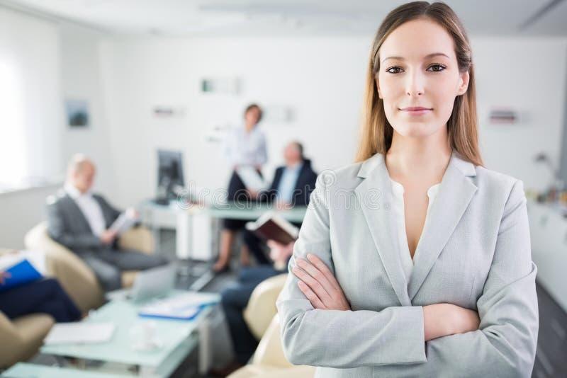 确信的在办公室横渡的女实业家常设胳膊 免版税库存图片