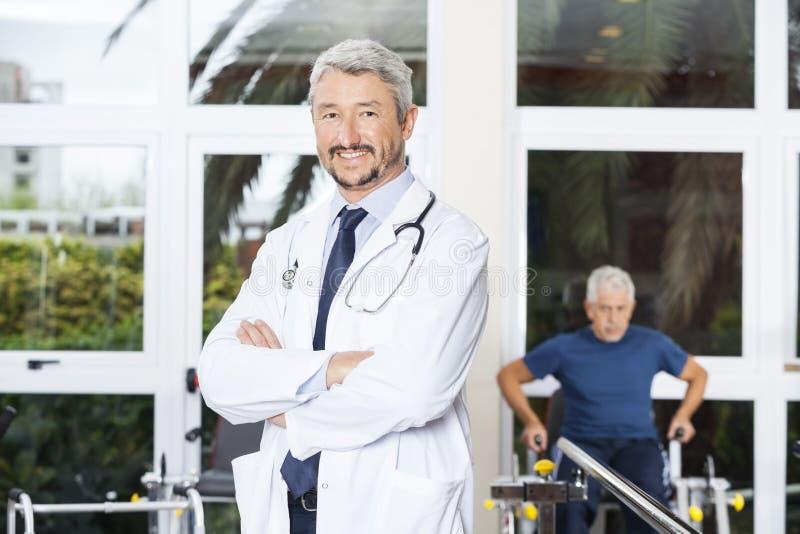 确信的在康复中心横渡的生理治疗师常设胳膊 免版税库存图片