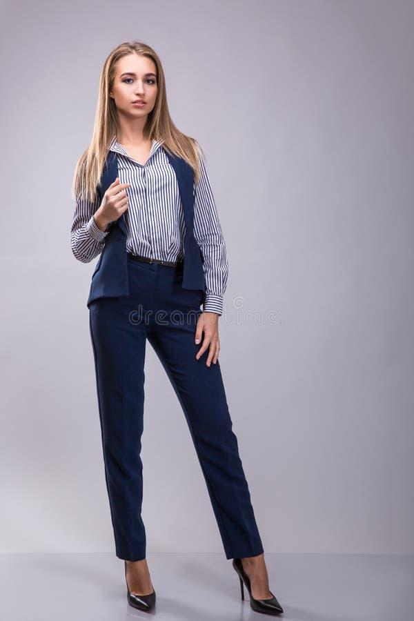 确信的女商人站立的佩带的典雅的衣裳或穿戴在灰色背景的西装 免版税库存照片