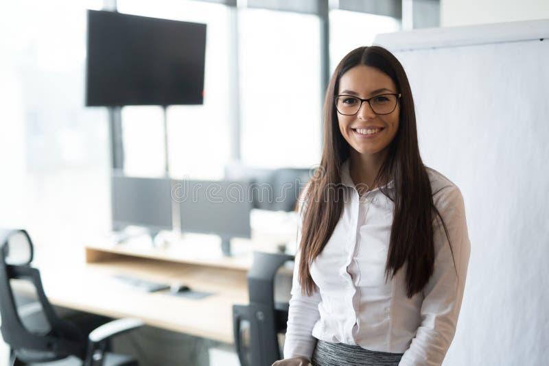 确信的女实业家佩带的玻璃在办公室 免版税库存图片