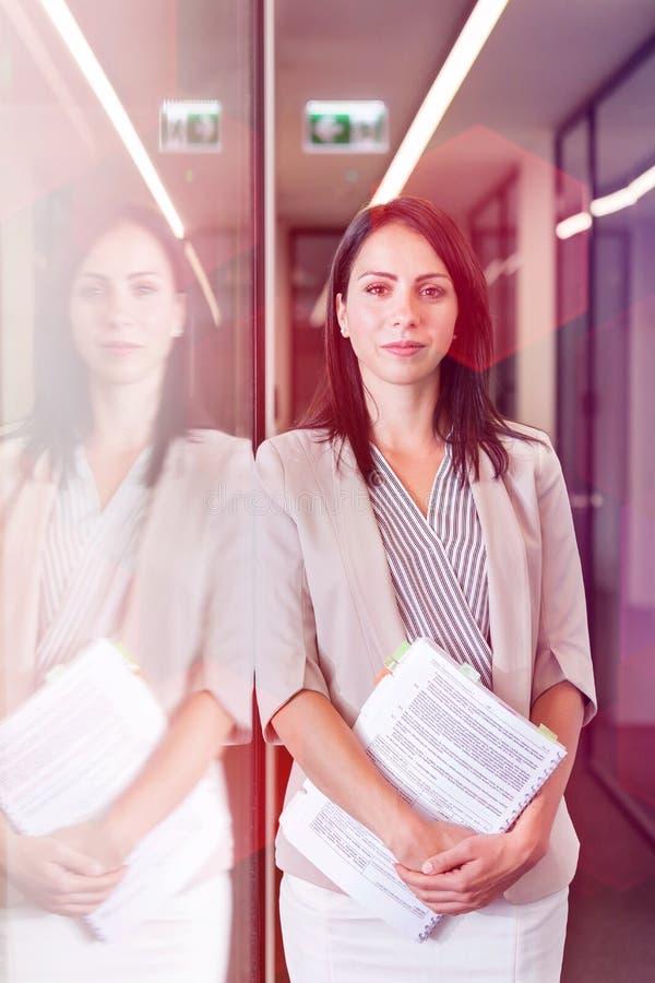 确信的女实业家身分画象与文件的在办公室 免版税库存照片