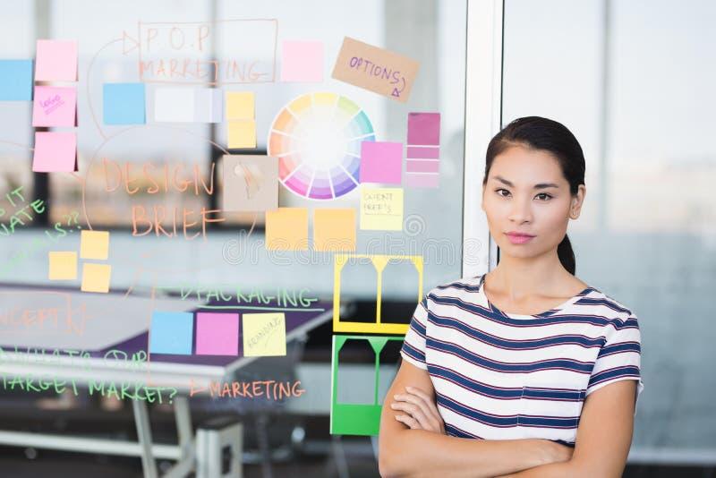 确信的女实业家画象由计划的在墙壁上 库存照片