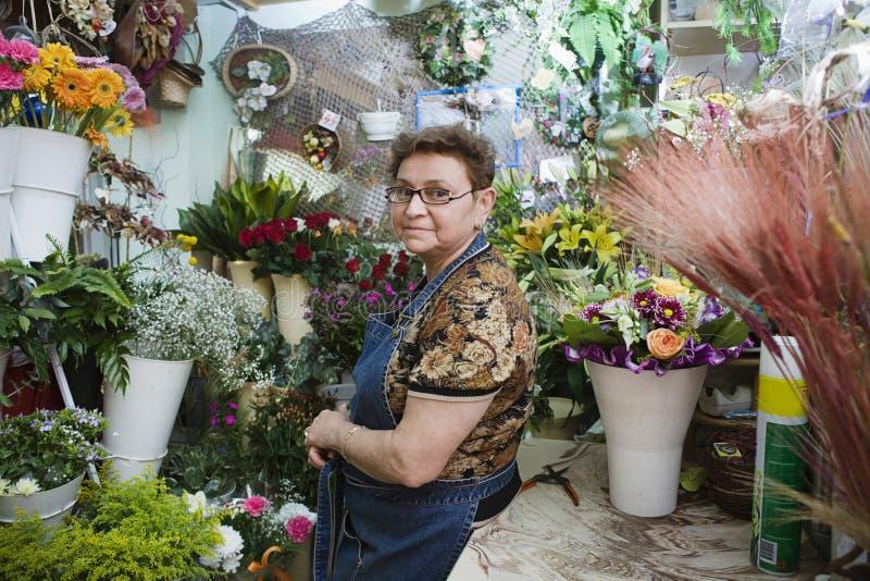 确信的女性卖花人在商店 图库摄影