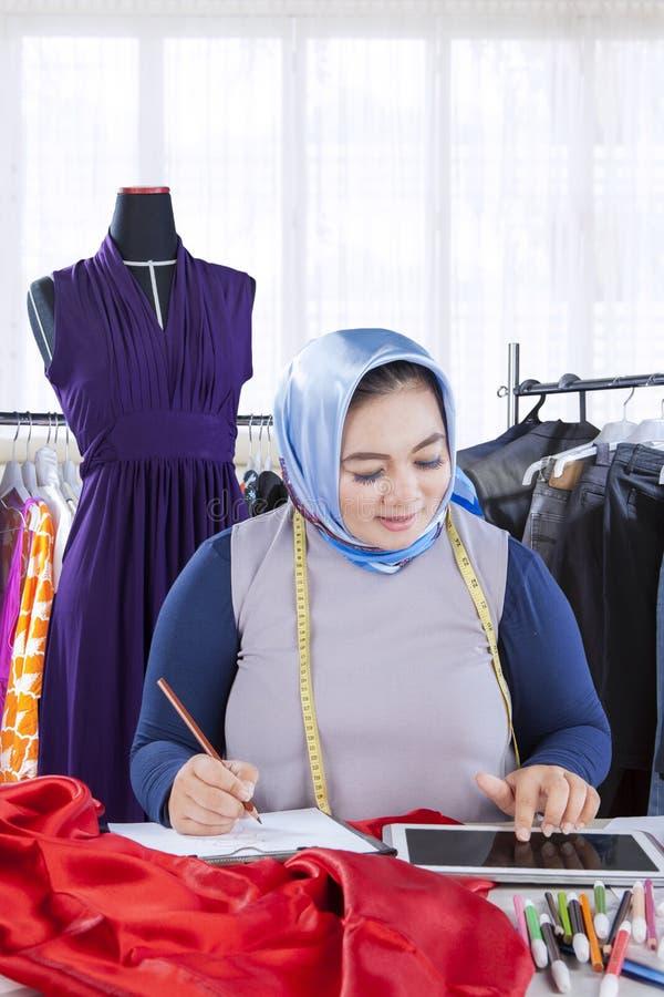确信的女性回教时装设计师与服装一起使用 免版税库存图片