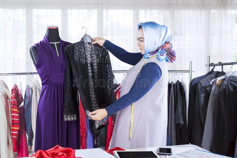确信的女性回教时装设计师与服装一起使用 库存图片