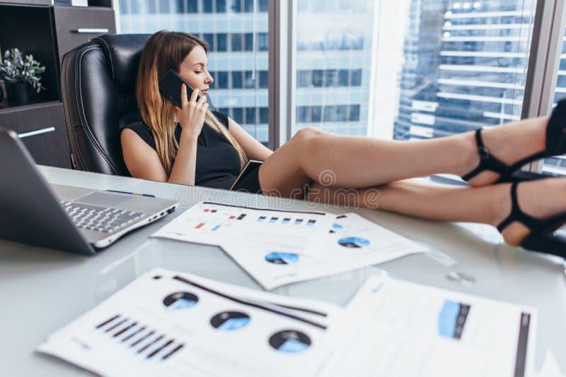 确信的女性首席执行官谈话在电话,当坐与她的脚在书桌在工作时 免版税图库摄影