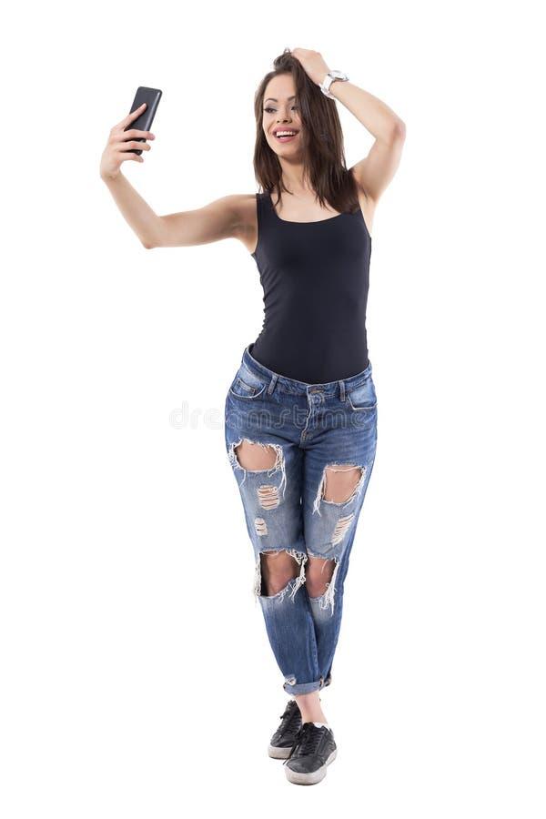 确信的妇女用在拍照片传讯的头发的手selfie照片与男朋友 免版税库存图片