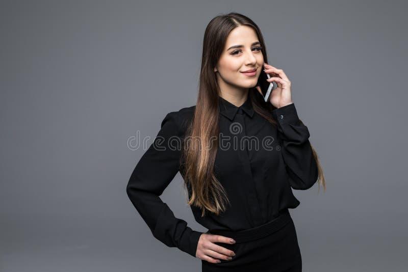 确信的少妇谈话在手机,当站立反对灰色背景时 免版税库存图片