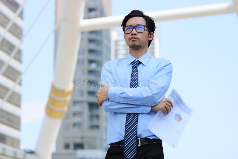 确信的年轻亚洲商人画象在都市大厦背景的 视觉企业概念 库存图片