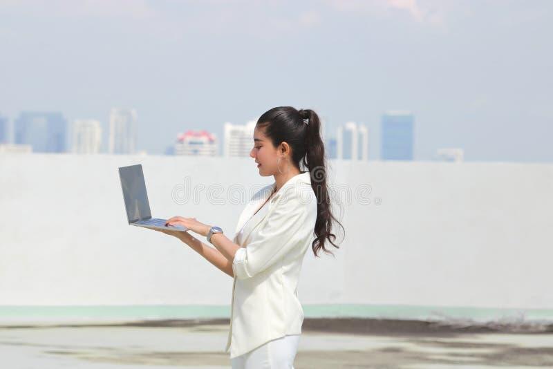 确信的年轻亚洲女商人藏品膝上型计算机用手 互联网和技术概念 免版税库存照片