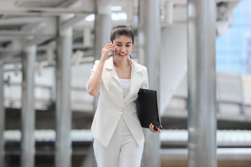 确信的年轻亚裔女商人谈话在电话在走期间与办公室 库存图片